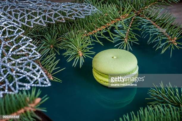 Fresh green almond macaroon pastry on Christmas table decorated with fir branches. Copy space.