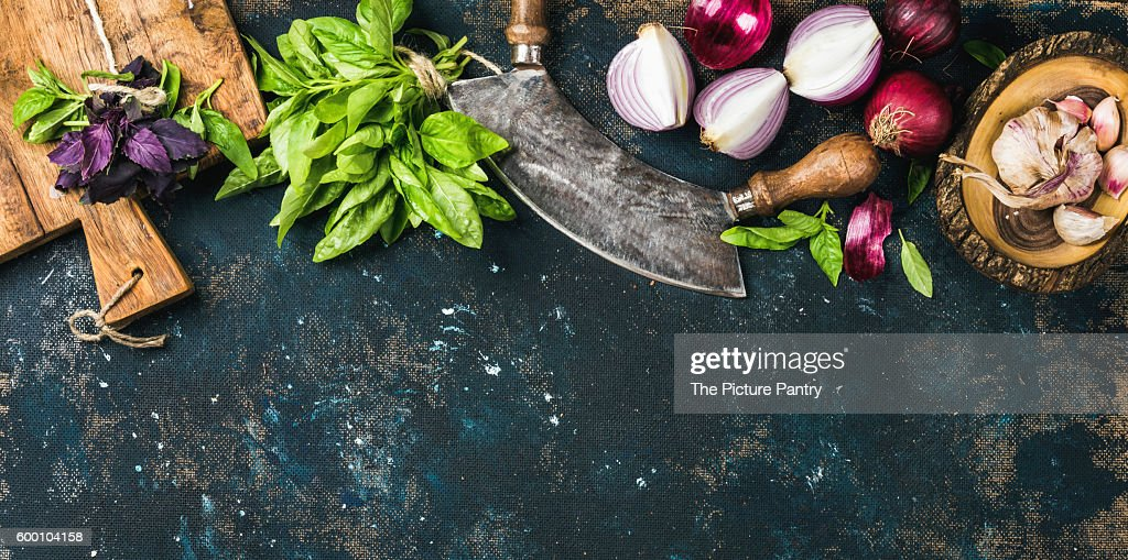 Fresh green and purple basil leaves, red onions and garlic with herb chopper knife and rustic cutting board over grunge dark blue plywood texture : Stock Photo