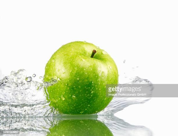 Fresh green apple with splashing water