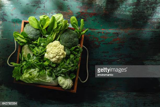 fresh green leaf vegetables in an old wooden crate on an old wooden turquoise table. - crucifers stock pictures, royalty-free photos & images
