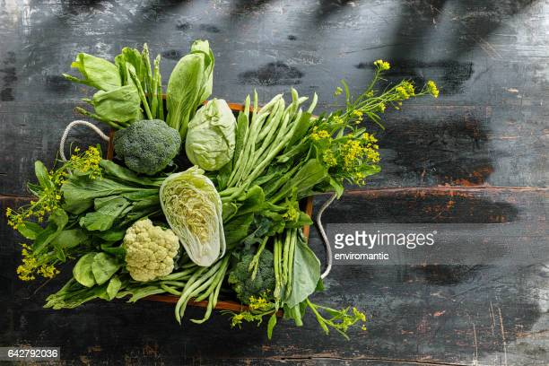 Fresh green leaf vegetables in an old wooden crate on an old wooden table.