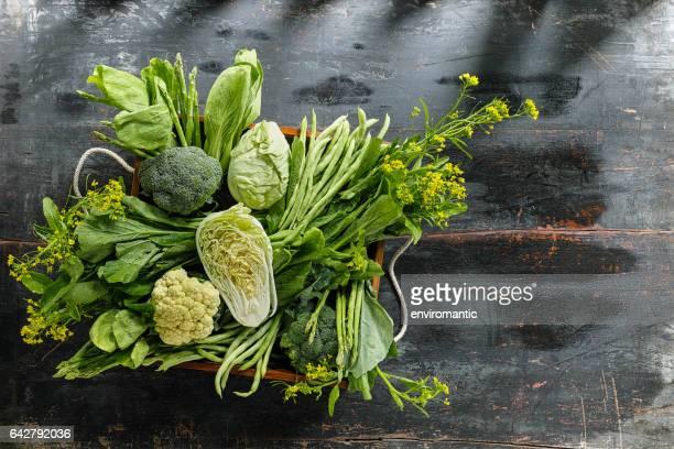 Frisches grünes Blattgemüse in einer alten Holzkiste auf einem alten Holztisch.