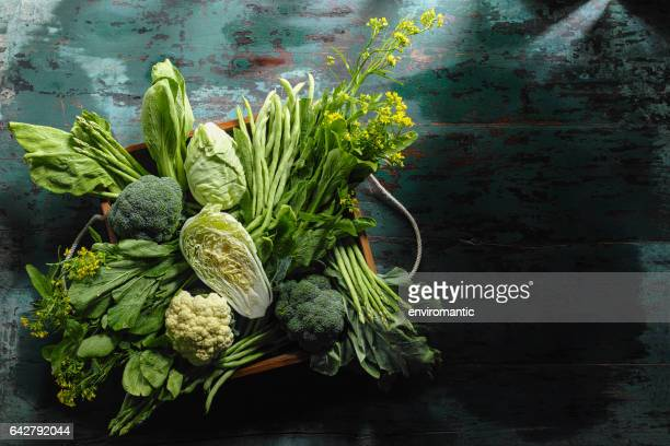 Fresh green leaf vegetables in an old wooden crate on an old wooden turquoise table.