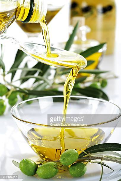 Fresh green olives and olive oil in glass bowl, close-up