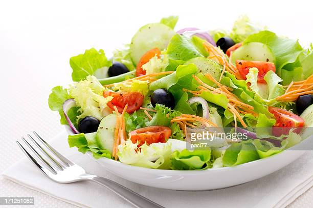 Fresh green salad with a fork in a white bowl