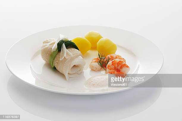Fresh halibut with with gambas and salt potatoes in plate on white background