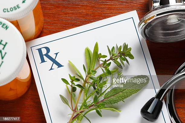 fresh herbs on top of a doctor's prescription pad - alternatieve geneeswijzen stockfoto's en -beelden