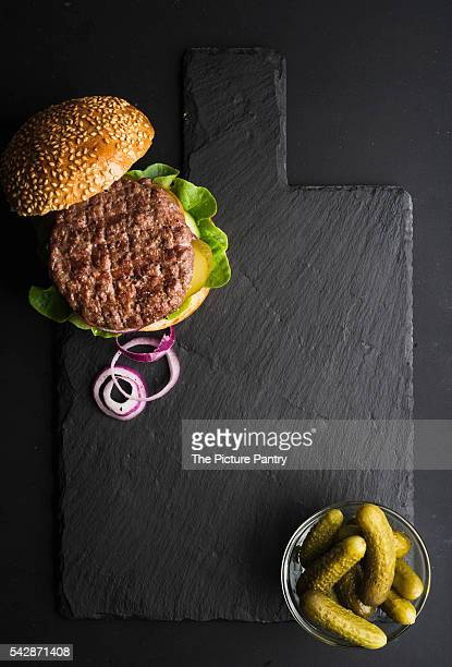 Fresh homemade burger on dark slate stone board, pickles and sliced onion over black background.