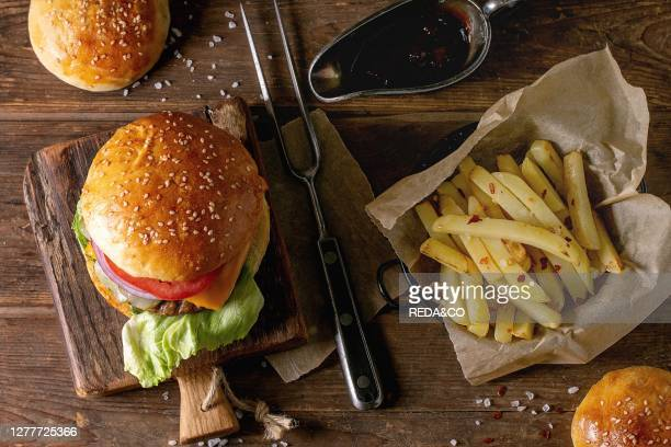 Fresh homemade burger on little cutting board and raw cutlet and sliced onion served with ketchup sauce and meat fork over wooden table Dark rustic...