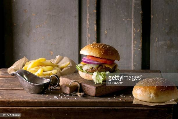 Fresh homemade burger on little cutting board with grilled potatoes served with ketchup sauce and sea salt over wooden table with gray wooden...