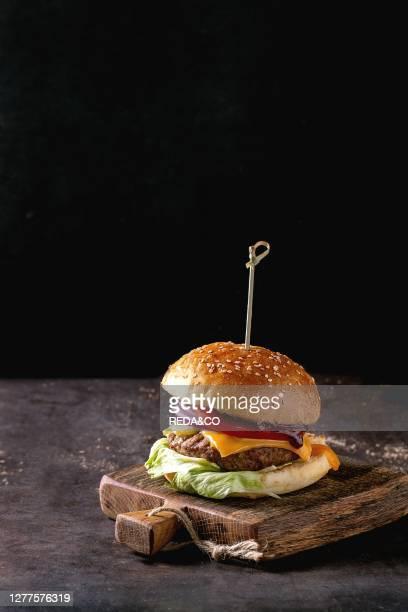 Fresh homemade burger on little wooden cutting board over dark background.