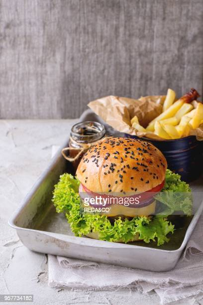 Fresh homemade burger with black sesame seeds in old aluminum tray with fried potatoes served with ketchup sauce in glass jar over white plastered...