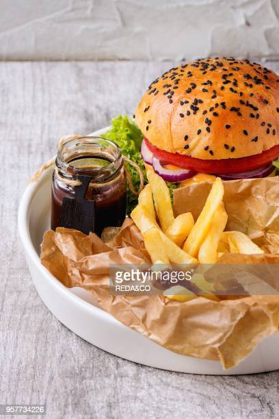 Fresh homemade burger with black sesame seeds in white plate with fried potatoes served with ketchup sauce in glass jar over gray wooden table