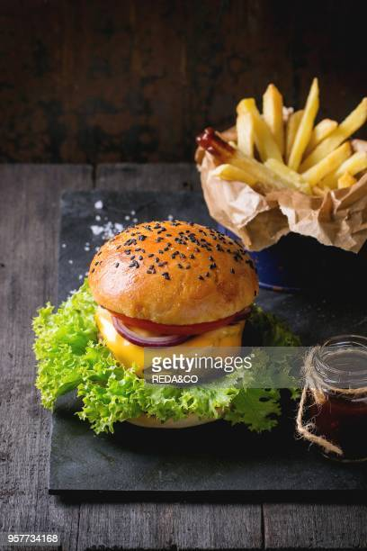 Fresh homemade burger with black sesame seeds on black slate board with fried potatoes served with ketchup sauce in glass jar and sea salt over old...