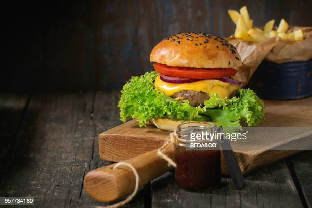 Fresh homemade burger with black sesame seeds on wooden cutting board with fried potatoes served with ketchup sauce in glass jar over old wooden...