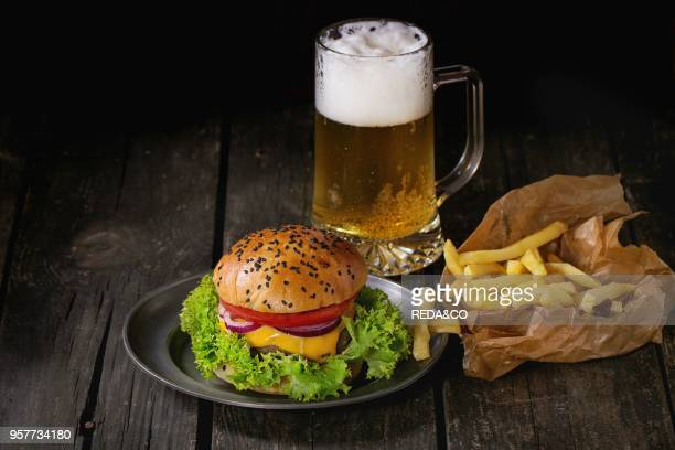 Fresh homemade burger with in old metal plate with french fries potatoes in baking paper served with glass of cold lager beer over old wooden table...