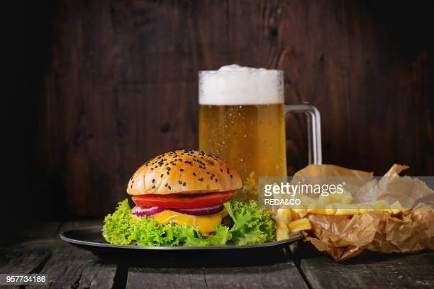 Fresh homemade burger with in old metal plate with fried potatoes in baking paper served with glass of cold lager beer over old wooden table with...