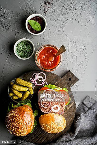 Fresh homemade burgers on dark serving board with spicy tomato sauce, green salt, pepper, pickles and onion over concrete textured background.