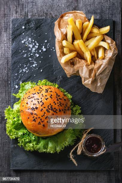 Fresh homemade hamburger with black sesame seeds and french fries potatoes in backing paper served with ketchup sauce in glass jar and sea salt on...