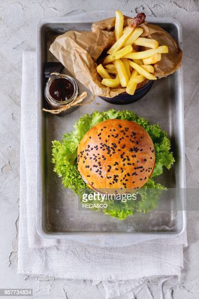Fresh homemade hamburger with black sesame seeds in old aluminum tray with fried potatoes served with ketchup sauce in glass jar over gray plastered...