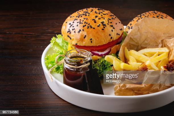 Fresh homemade hamburger with black sesame seeds in white plate with french fries potatoes served with ketchup sauce in glass jar over dark wooden...