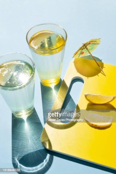 fresh homemade lemonade glasses on blue colored background - lemon soda stock pictures, royalty-free photos & images