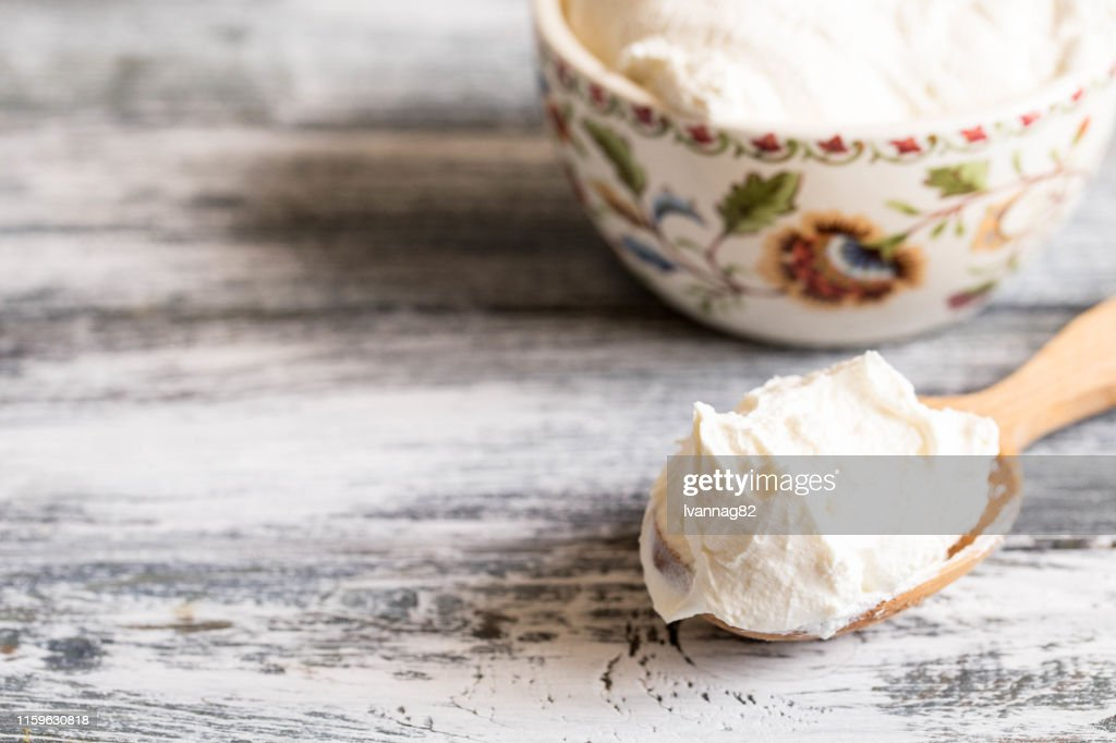 Fresh homemade mascarpone. Traditional Mascarpone cheese in wooden spoon : Stock Photo