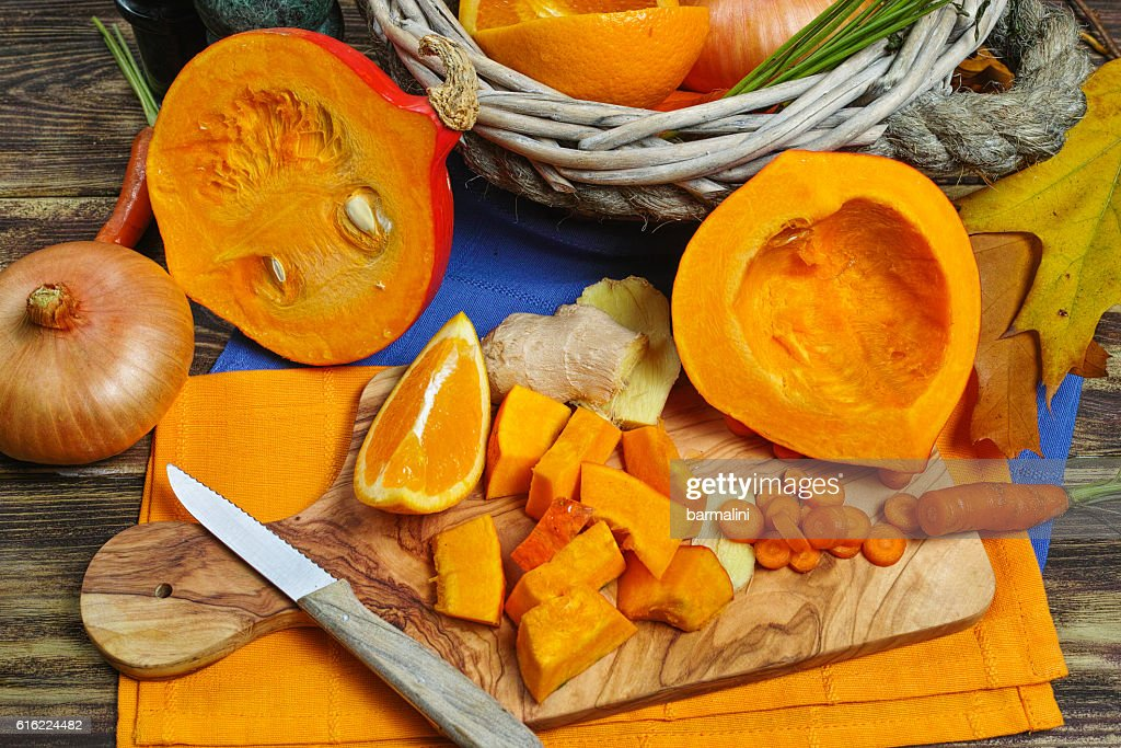 Fresh ingredients for pumpkin soup - apple, orange, carrot, onion : Stock-Foto