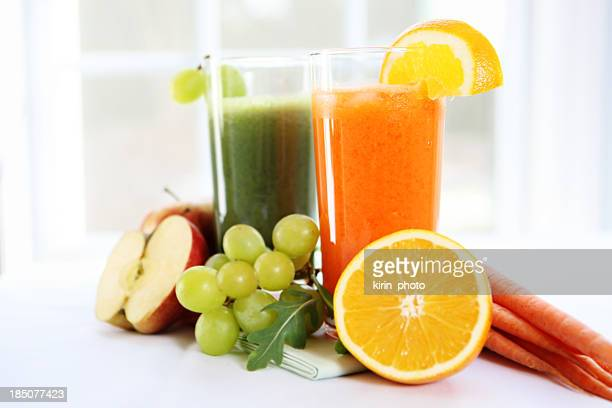 Fresh juice in glasses surrounded by fruits and vegetables