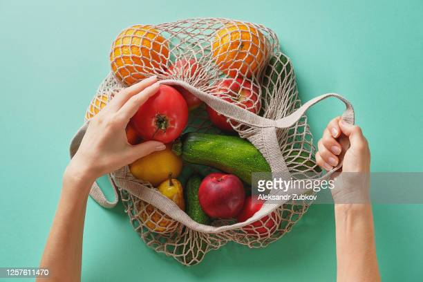 fresh juicy fruits and vegetables, products in a reusable shopping bag. a girl or woman takes or lays out products from a string bag made from recycled materials on a green pastel background. vegetarianism, veganism. no plastic. - fruit stock pictures, royalty-free photos & images