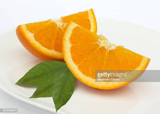 Fresh, juicy orange quarters with leaves