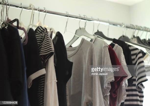 fresh laundry drying out on hangers in laundry room, clothes with pale colours - 乾かす ストックフォトと画像