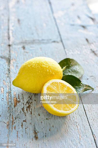 fresh lemons on blue rustic table - lemon leaf stock photos and pictures