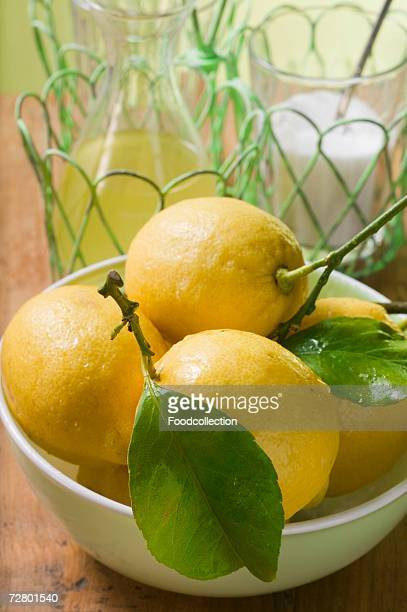 Fresh lemons with leaves in bowl, lemon juice, sugar
