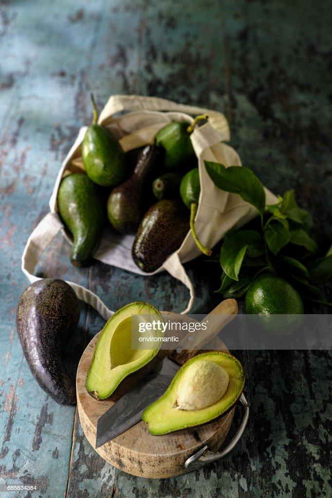 Frischmarkt Avocado halbieren auf einem Holzbrett neben einem Messer mit mehr Avocados im Hintergrund in eine wiederverwendbare Einkaufstasche aus Baumwolle. : Stock-Foto