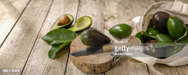 Fresh market avocado on a wooden cutting board next to a knife with more avocados in a cotton reusable shopping bag to the right of the image.