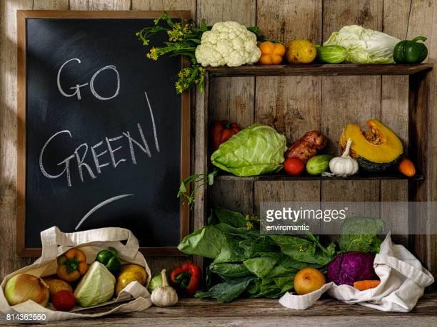 古い素朴な木製の棚とテーブルと行く緑の古い木の板壁を背景にチョークで書かれた黒板の横に、再利用可能なコットン ショッピング バッグのいくつかの新鮮野菜。