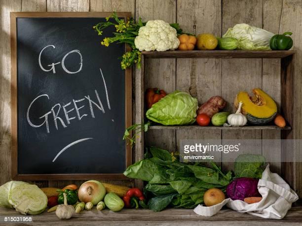 古い素朴な木製の棚とテーブルと行く緑の! 古い木の板壁を背景に白いチョークで書かれた黒板の横に、綿を再利用可能な買い物袋にいくつかの新鮮野菜。
