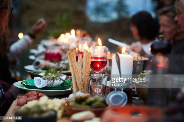 fresh meal and burning candles on dining table at farm during party - mensch im hintergrund stock-fotos und bilder