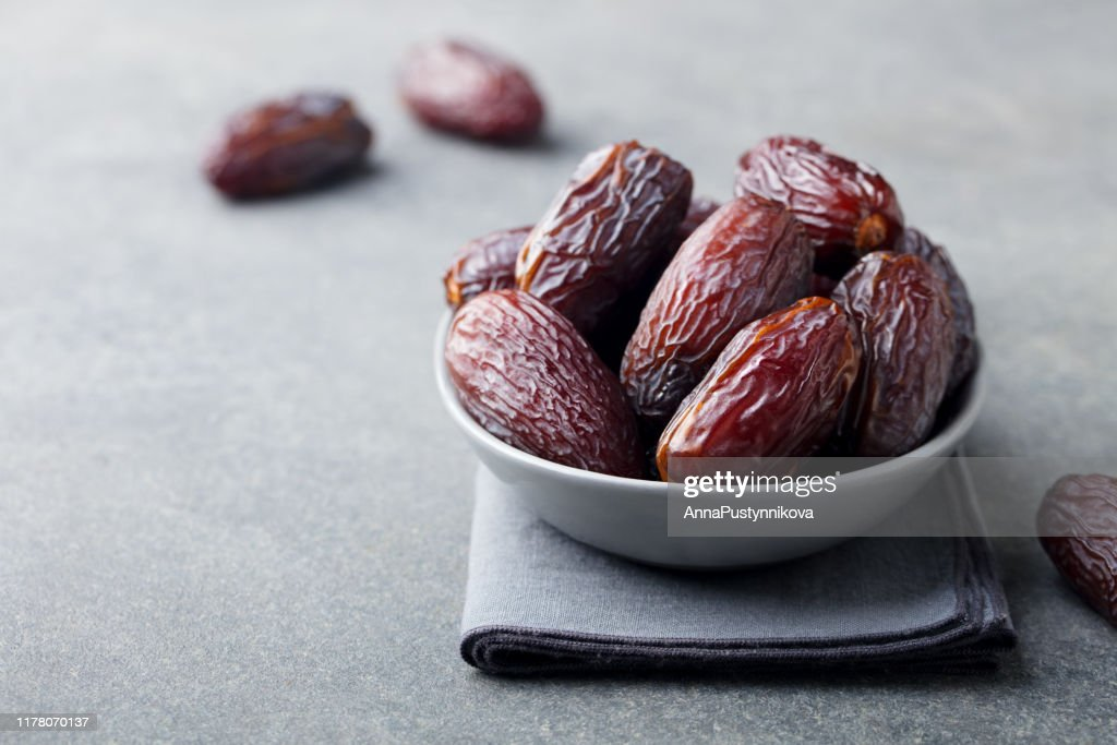 Fresh medjool dates in bowl. Grey background. Copy space. : Stock Photo