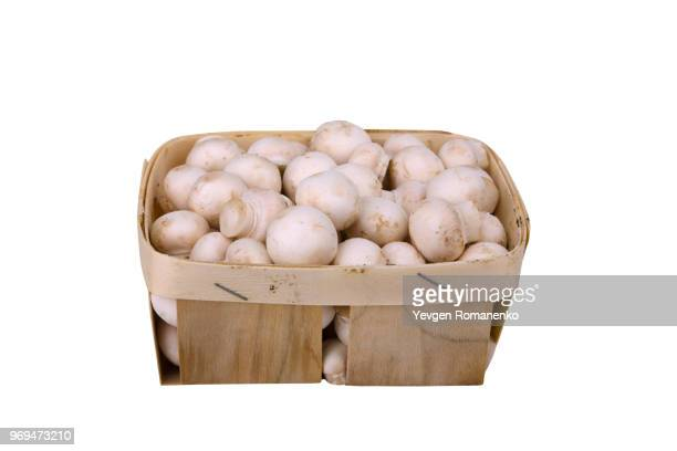 Fresh mushrooms in a wooden box isolated on white