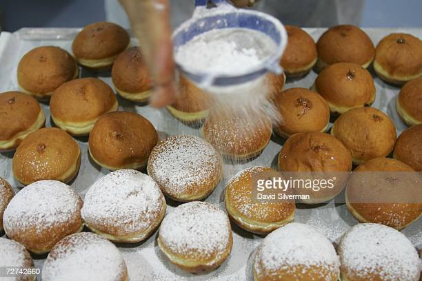 Fresh oil-fried doughnuts, called sufganiyot in Hebrew, are dusted with icing sugar before going on display at the Roladin bakery December 6, 2006 in...