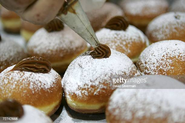 Fresh oil-fried doughnuts, called sufganiyot in Hebrew, are filled with caramel before going on display at the Roladin bakery December 6, 2006 in...