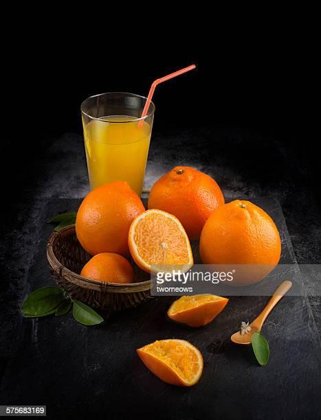 Fresh orange and juice on moody background