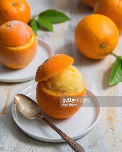 fresh orange sorbet with spoon in white background - sorbet stock pictures, royalty-free photos & images