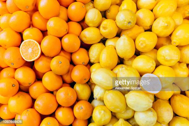 fresh oranges and lemons on a market stall - orange fruit stock pictures, royalty-free photos & images