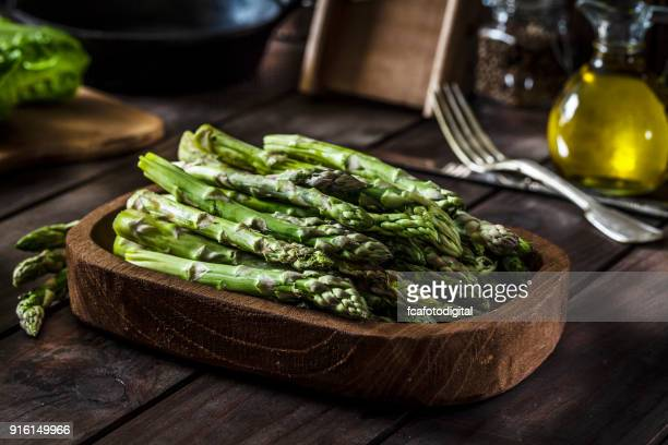 Fresh organic asparagus shot on rustic wooden table