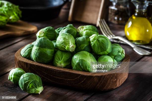 Fresh organic Brussels sprouts shot on rustic wooden table