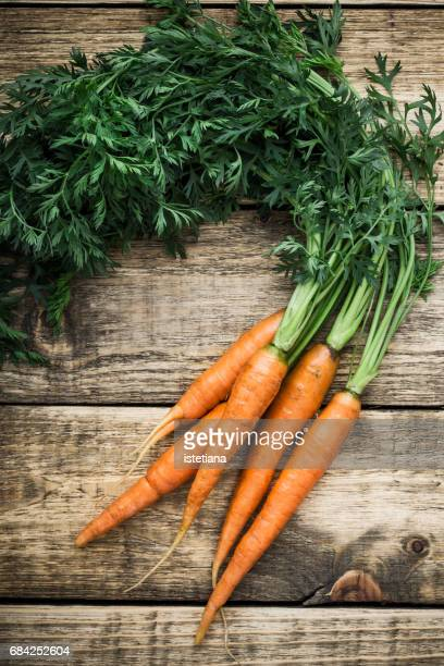 Fresh organic carrots over wooden background