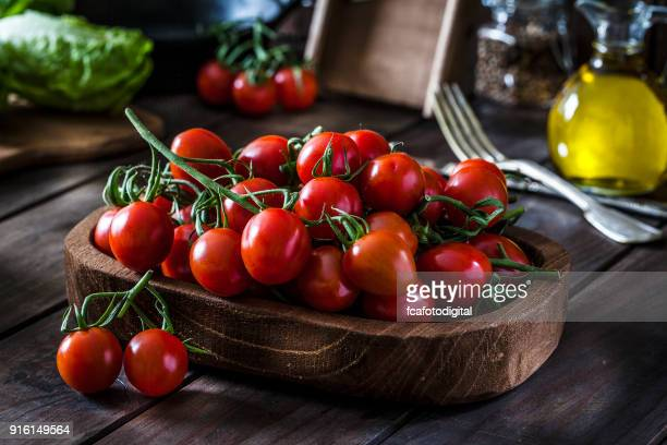 Fresh organic cherry tomatoes shot on rustic wooden table